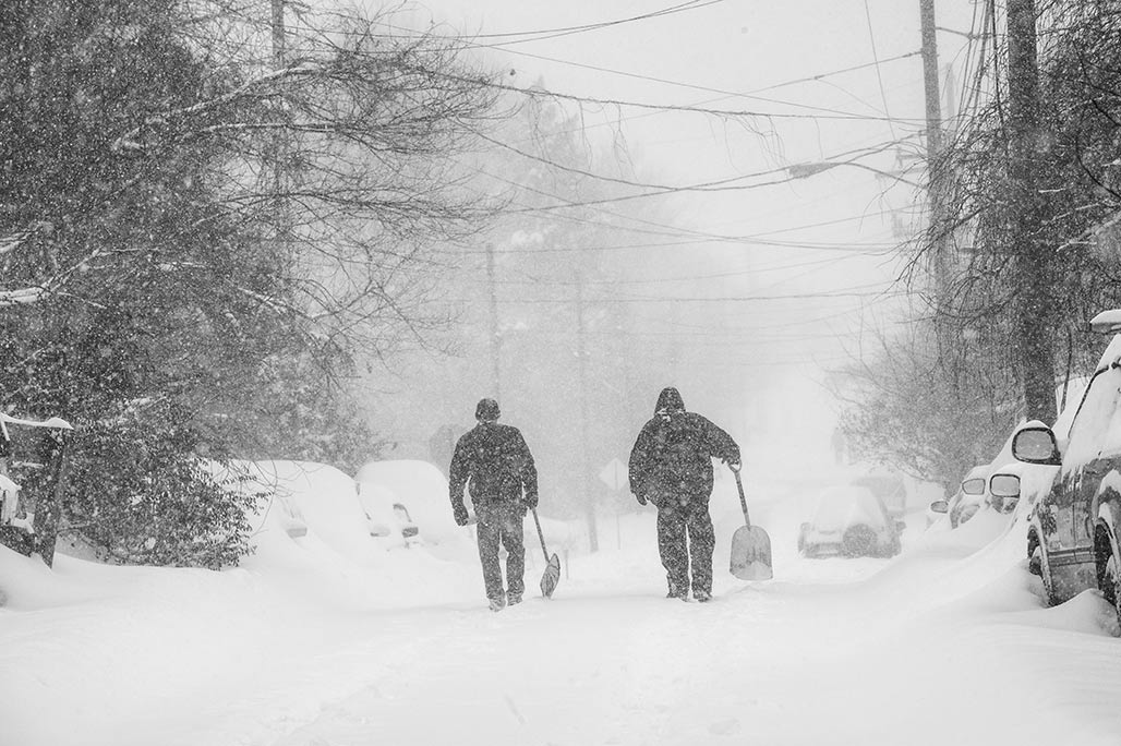 snow shovelers walk the street