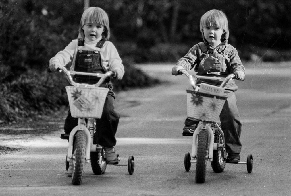 twins riding bikes with training wheels