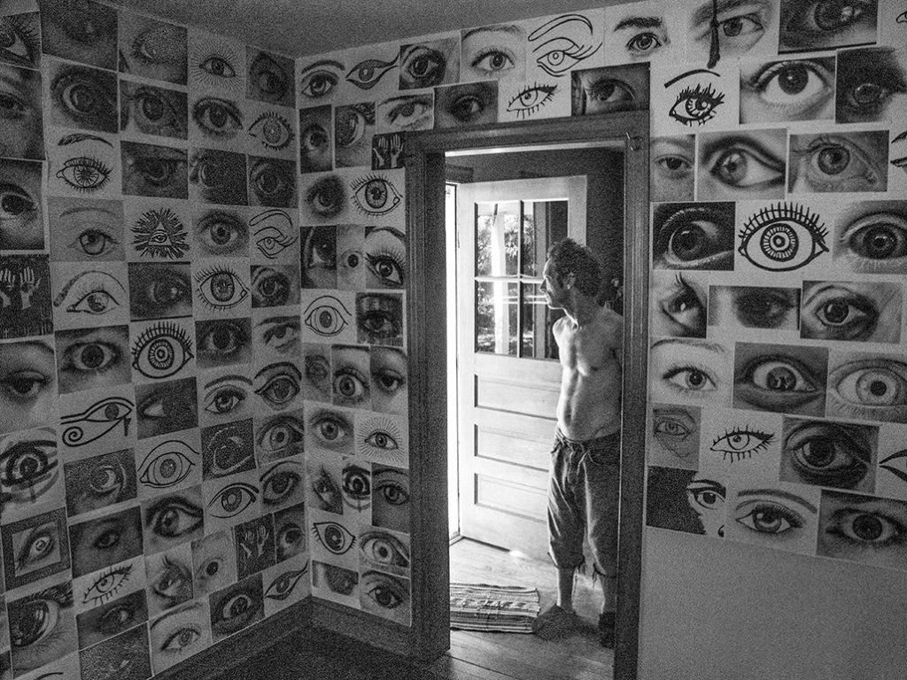 man in open door background room with 2d representations of eyes on the walls, foreground